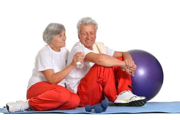Pareja de ancianos haciendo ejercicio, sentado en el suelo de un gimnasio aislado en blanco