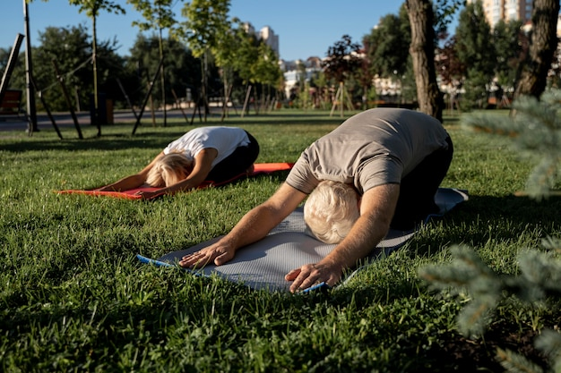 Pareja de ancianos haciendo yoga afuera