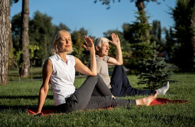 Pareja de ancianos haciendo yoga al aire libre