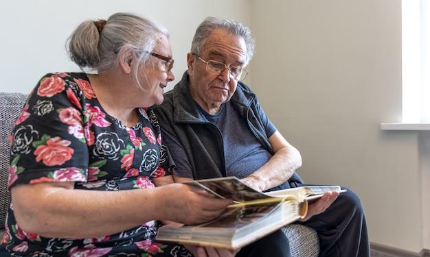 Una pareja de ancianos está mirando fotografías en un álbum de fotos familiar.
