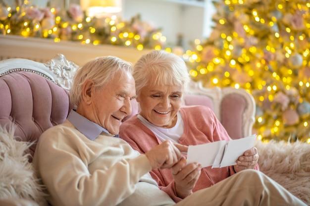 Pareja de ancianos mirando a través de fotografías antiguas