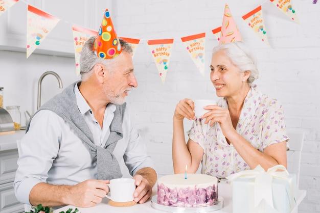 Pareja de ancianos mirándose mientras se toma una taza de café durante la fiesta de cumpleaños