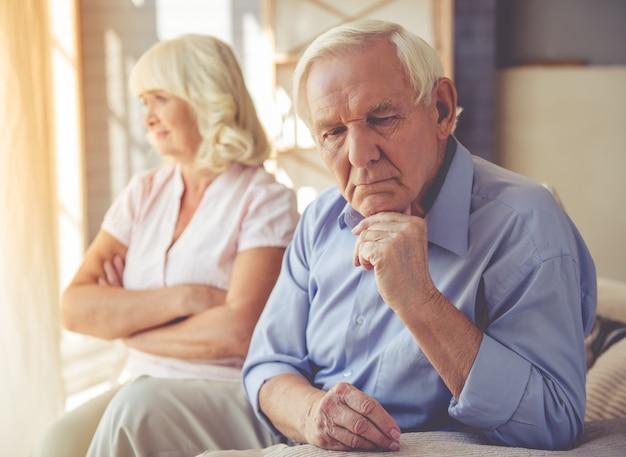 Pareja de ancianos pensativa está sentada aparte en el sofá