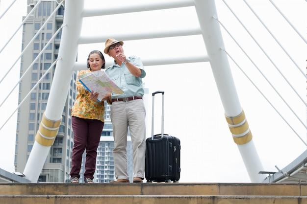 La pareja de ancianos está de pie sosteniendo el mapa para buscar destinos en las calles.