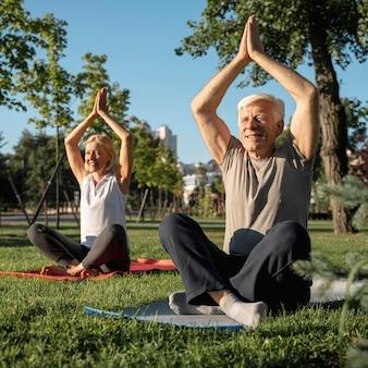Pareja de ancianos practicando yoga al aire libre