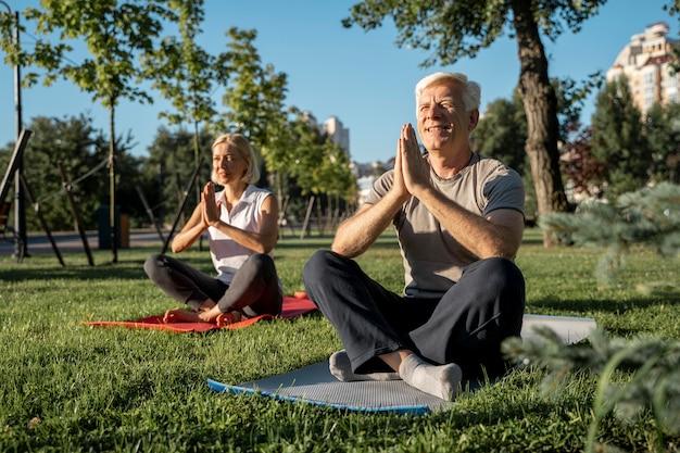 Pareja de ancianos practicando yoga fuera