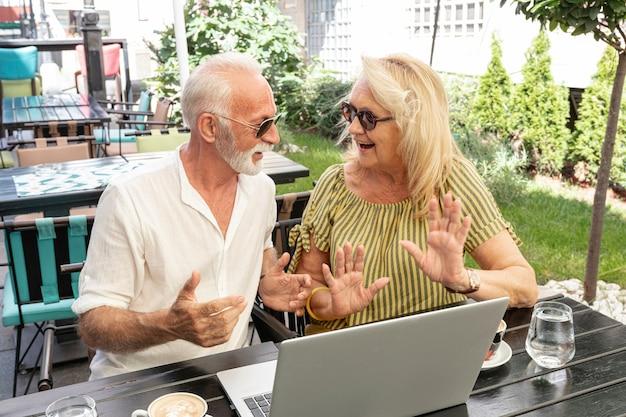 Pareja de ancianos riéndose juntos delante de una computadora portátil