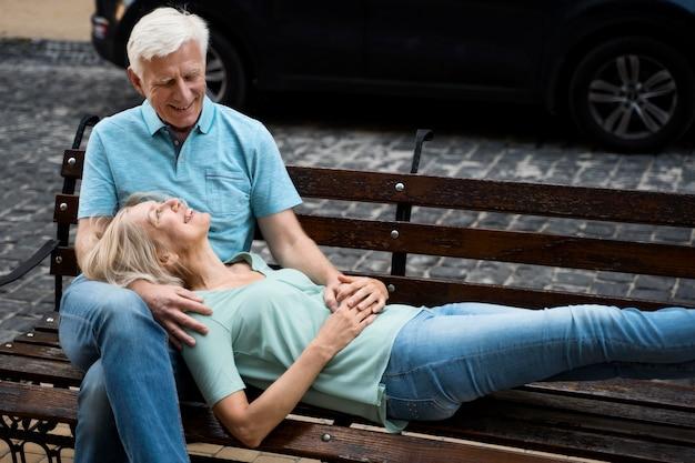 Pareja de ancianos romántica disfrutando de su tiempo en un banco al aire libre