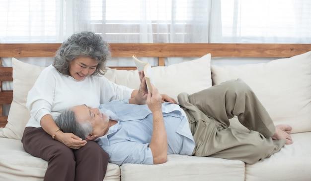 Pareja de ancianos sentados en el sofá lee el libro en casa