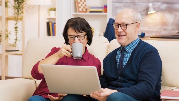 Pareja de ancianos sentados en el sofá sosteniendo el portátil durante una videollamada. pareja saludando a la computadora portátil.