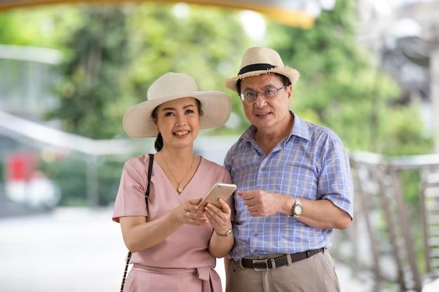 Pareja de ancianos con sombrero de pie al aire libre en el teléfono móvil.
