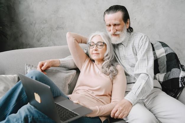 Pareja de ancianos sonriendo y mirando la misma computadora portátil abrazados en el sofá