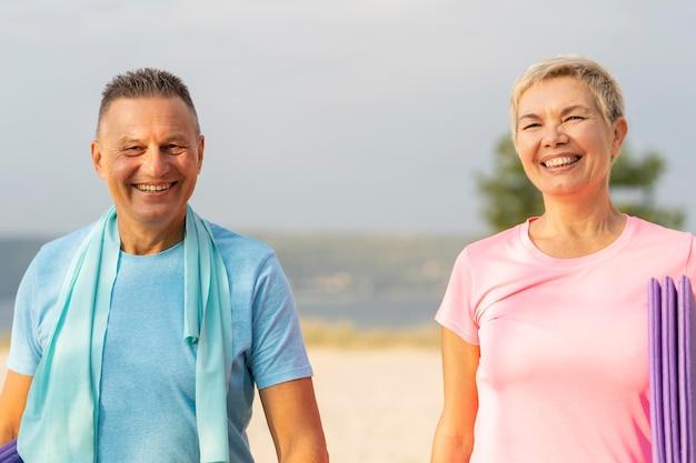 Pareja de ancianos sonriente con equipo de trabajo en la playa