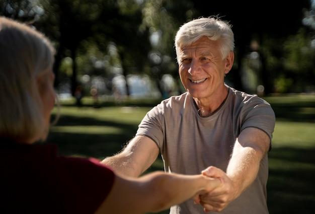 Pareja de ancianos sonriente haciendo ejercicio al aire libre