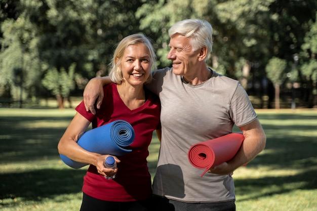 Pareja de ancianos sonrientes al aire libre con colchonetas de yoga y botella de agua