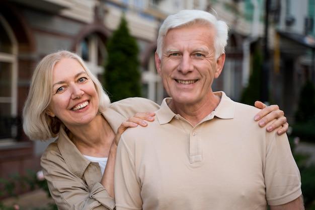 Pareja de ancianos sonrientes posando juntos mientras están en la ciudad
