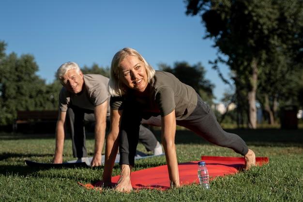 Pareja de ancianos sonrientes practicando yoga al aire libre