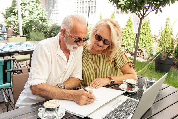 Pareja de ancianos tomando notas en agenda