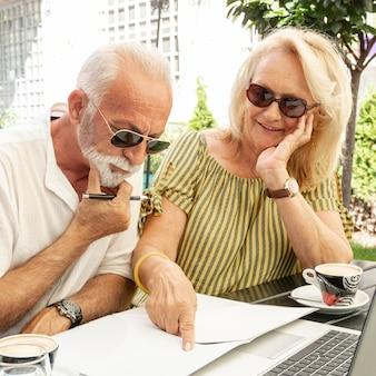 Pareja de ancianos tomando notas en la agenda