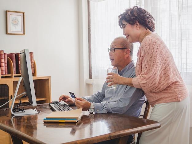 Pareja de ancianos usando la computadora junto con la tarjeta de crédito en casa