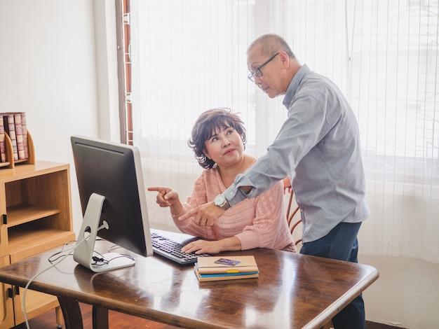 Pareja de ancianos usando la computadora junto con tarjeta de crédito en casa