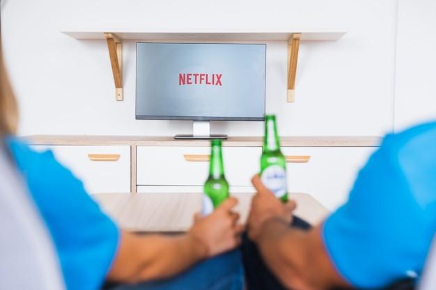 Pareja anónima con cerveza disfrutando de programas de televisión