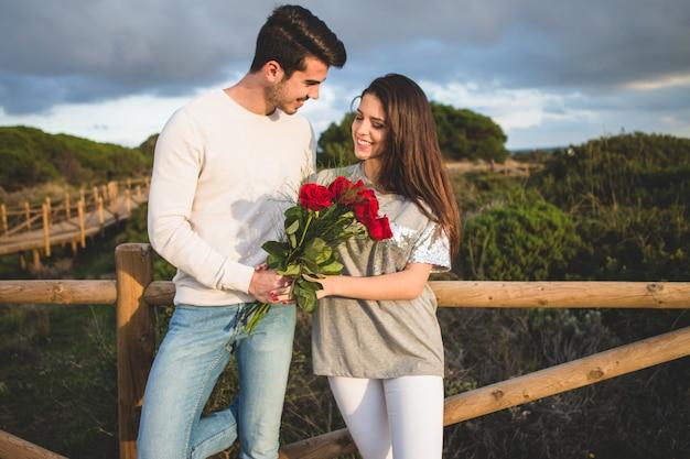 Pareja apoyada en una barandilla de un puente con un ramo de rosas