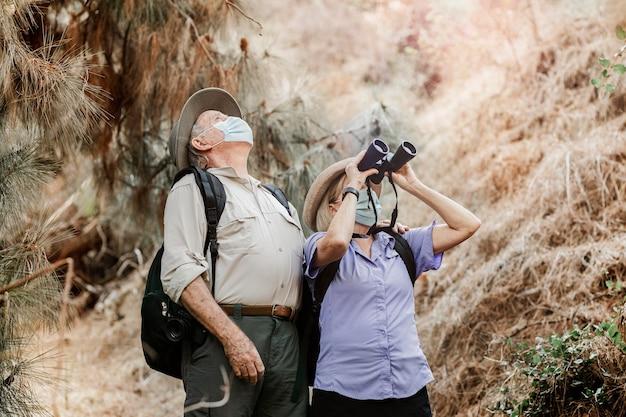 Pareja apreciando la belleza de la naturaleza con binoculares durante la nueva normalidad