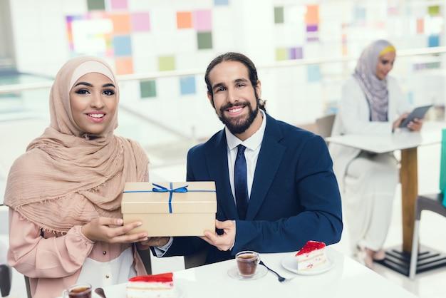 Pareja árabe con tazas de té y pastel