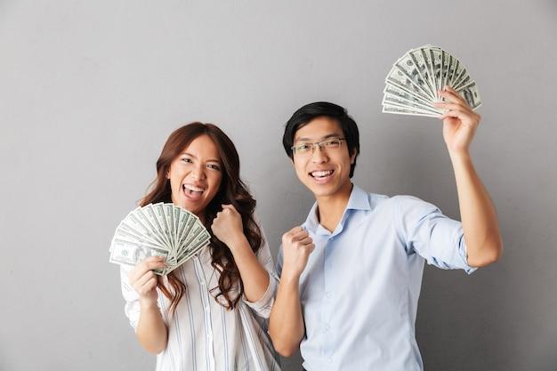 Pareja asiática alegre que se encuentran aisladas, sosteniendo billetes de dinero