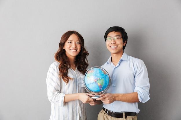 Pareja asiática alegre que se encuentran aisladas, sosteniendo el globo terráqueo