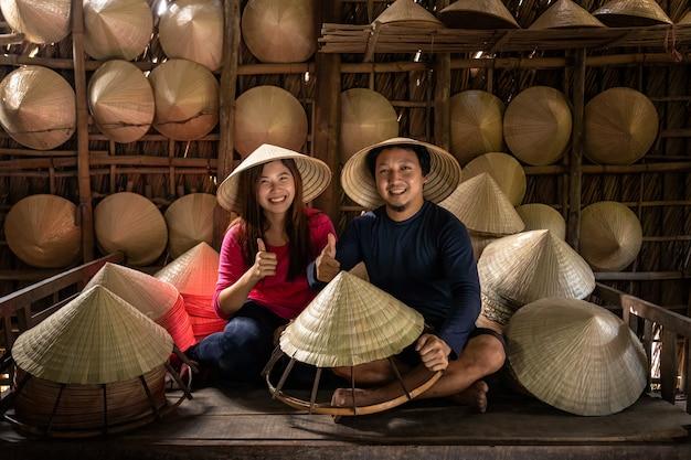 Pareja asiática artesano viajero haciendo el tradicional vietnam sombrero en la vieja casa tradicional