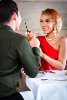 Pareja asiática bebiendo cócteles en el bar de lujo