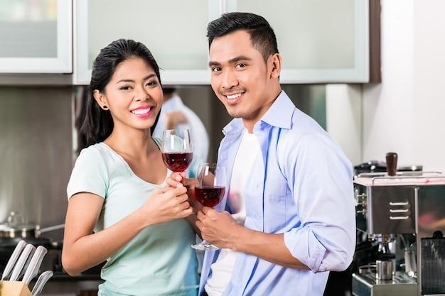 Pareja asiática bebiendo vino tinto en la cocina