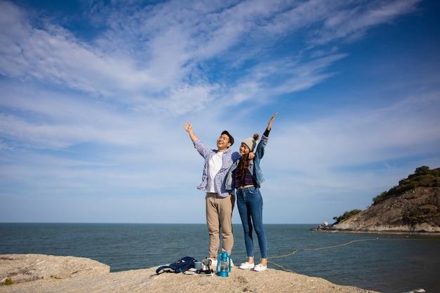 Pareja asiática en camisa azul con taza de café y picnic de cámara vintage en la montaña cerca de la playa vista al mar feliz y cara de sonrisa