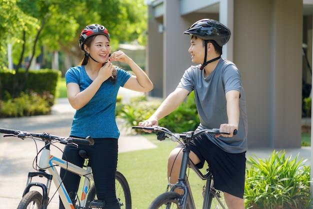 Pareja asiática con casco mientras se prepara para un paseo en bicicleta por su vecindario para la salud y el bienestar diario, tanto físico como mental.