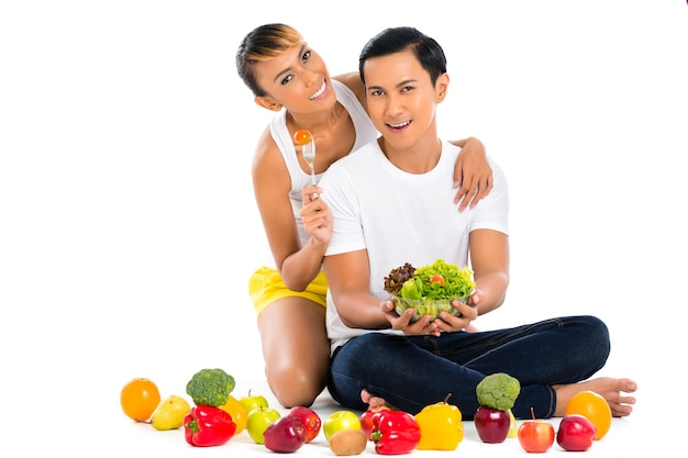 Pareja asiática comiendo ensalada de frutas y verduras