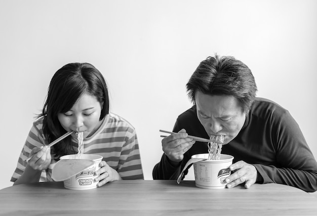 Pareja asiática comiendo fideos instantáneos