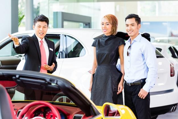 Pareja asiática comprando carro en concesionario