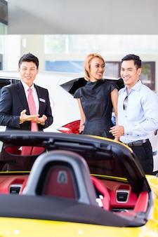 Pareja asiática comprando coche en concesionario de automóviles consultando al vendedor
