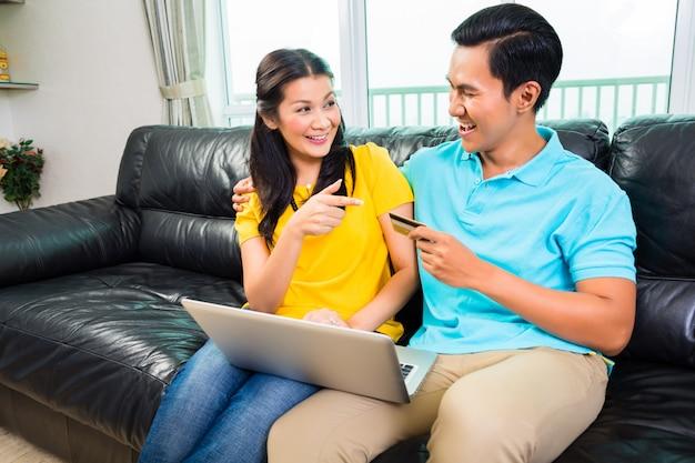 Pareja asiática de compras en línea con tarjeta de crédito