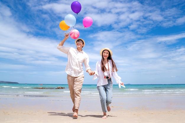 Pareja asiática corre y feliz en la playa de pattaya con globo en mano