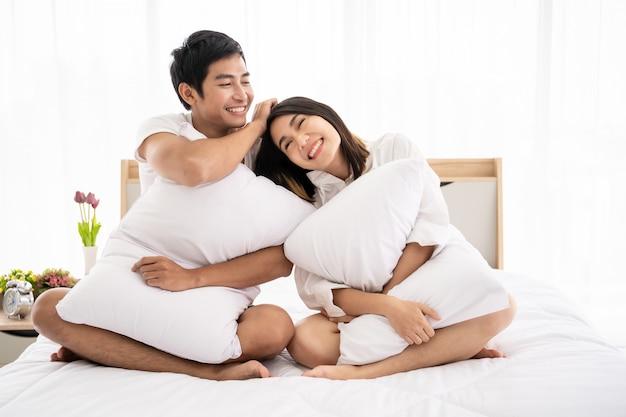 Pareja asiática divertida y romántica en dormitorio con luz natural