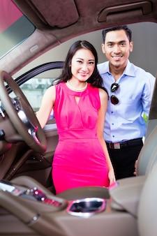 Pareja asiática eligiendo coches de lujo en concesionario de automóviles mirando el interior