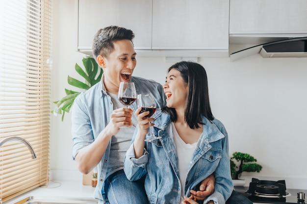 Pareja asiática enamorada riendo y bebiendo vino tinto en la cocina