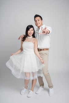 Pareja asiática enamorada en vestido de novia casual mostrando te amo gesto