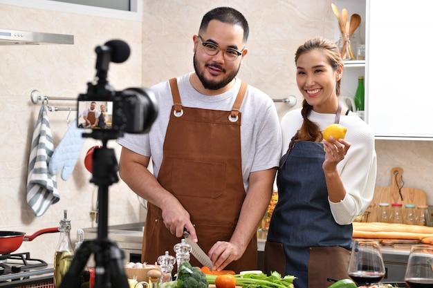Pareja asiática grabando un video en la cocina