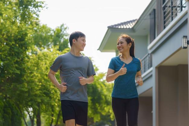 Una pareja asiática está haciendo jogging en el vecindario por su salud y bienestar diario, tanto físico como mental, y es un simple antídoto contra el estrés diario y para socializar de manera segura.