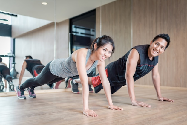Pareja asiática haciendo push up juntos en el gimnasio