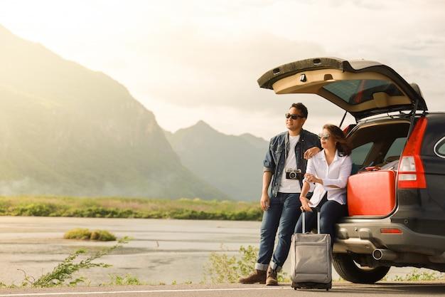 Pareja asiática hombre con cámara vintage y mujer sentada en la parte trasera del viaje en coche a la montaña y al lago en vacaciones con viaje en coche